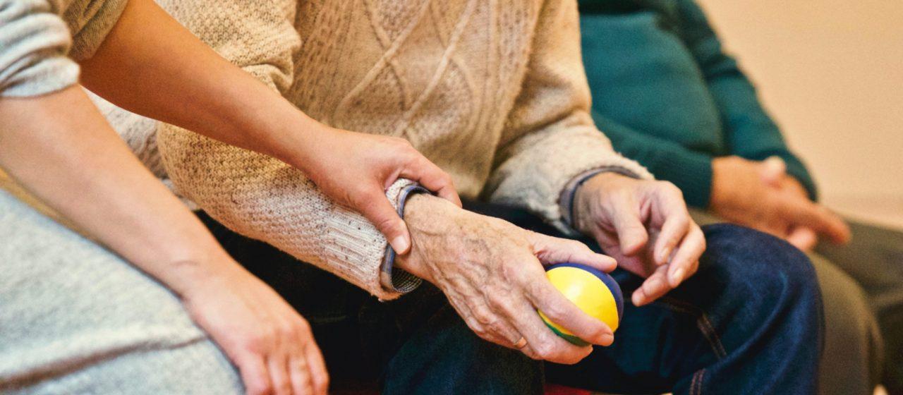 Starszy człowiek ugniata piłkę w ręku.