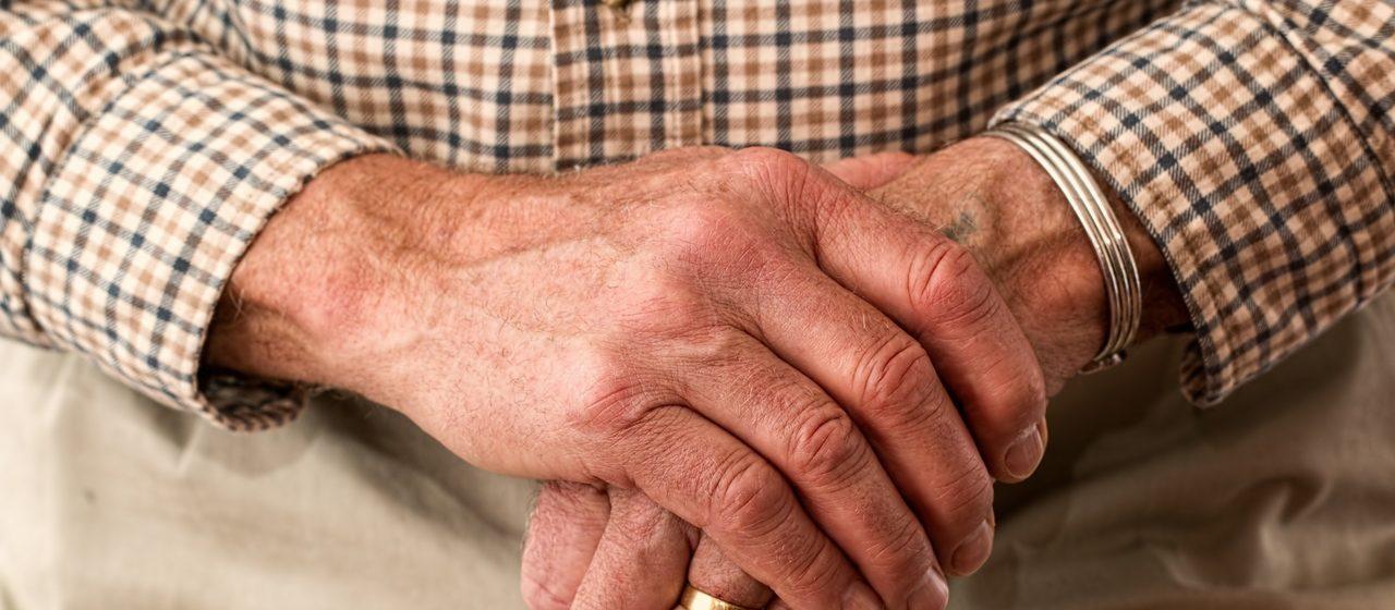 Starszy człowiek z obrączką trzyma laskę w ręku.