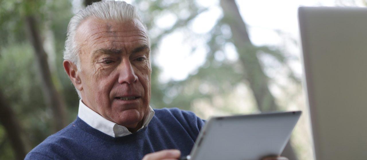 Starszy człowiek używa tabletu.